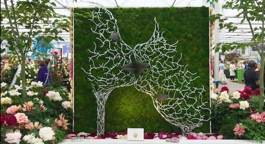 Bird Sculpture Against Green Moss