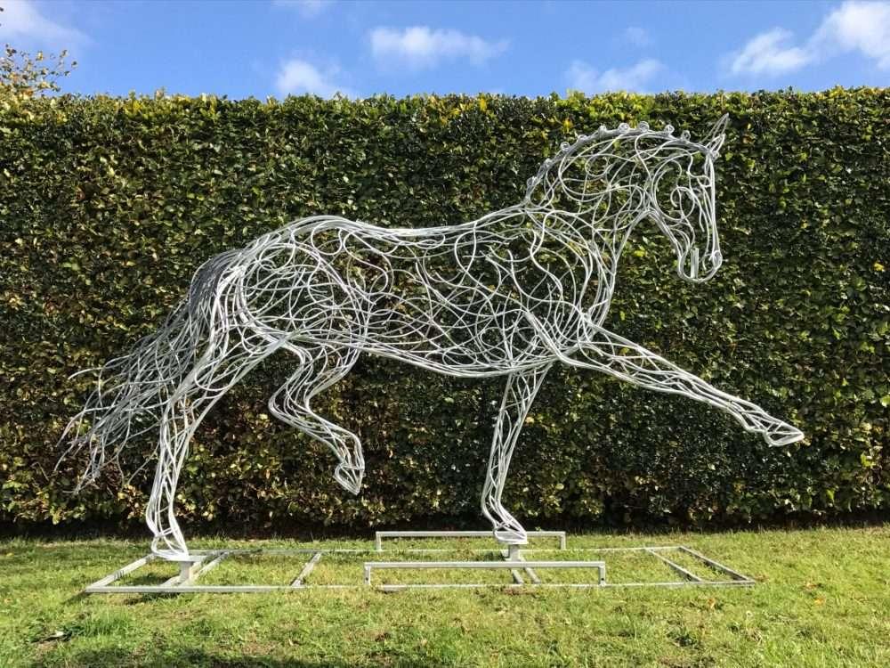 Horse Sculpture Against A Hedge