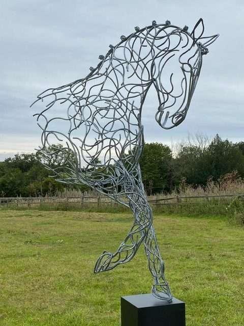 large half horse sculpture standing on black plinth
