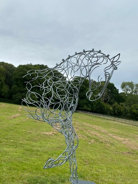 half horse sculpture in wooded area