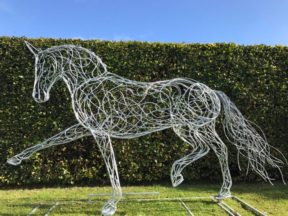 Horse Sculpture With Pointed Leg Against A Green Hedge