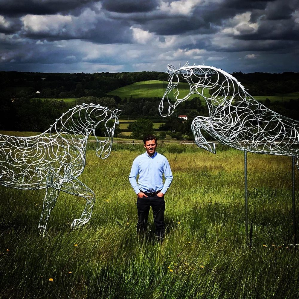 two horse sculptures with a man stood beside them