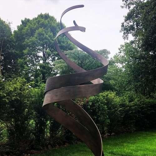 Bronze Patina Spiral Sculpture In Woodland