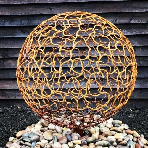 Rustic Sphere Sculpture On Rocks