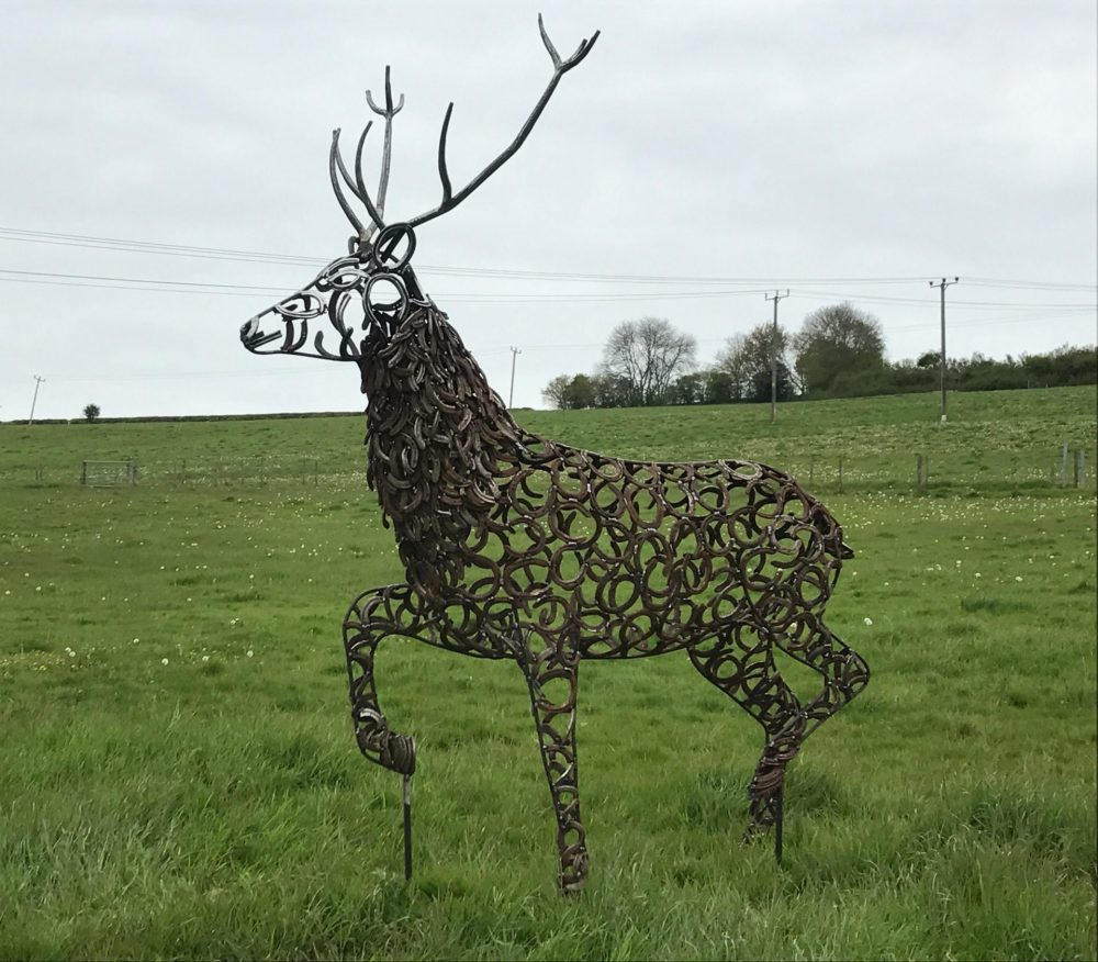 Strutting Stag Sculpture In Front Of Phone Lines