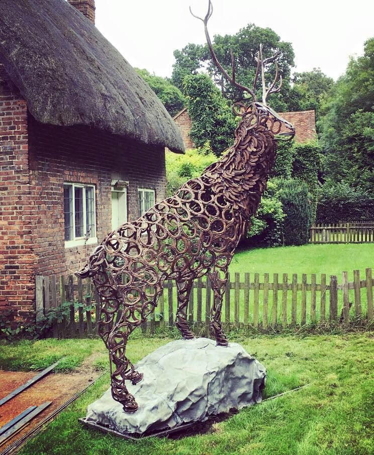 Stag Sculpture In Front Of Cottage