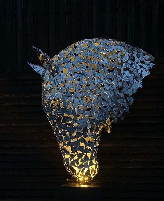 silver horse head being lit in darkness