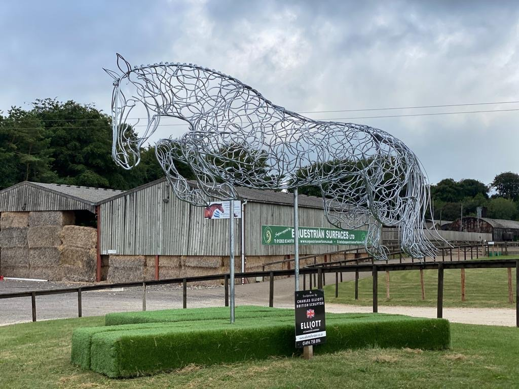 large horse jumping sculpture in front of barns