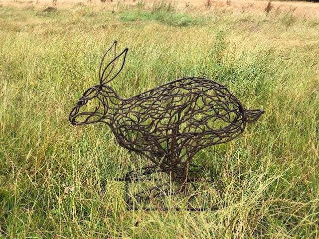 small bronze hare sculpture in tall grass