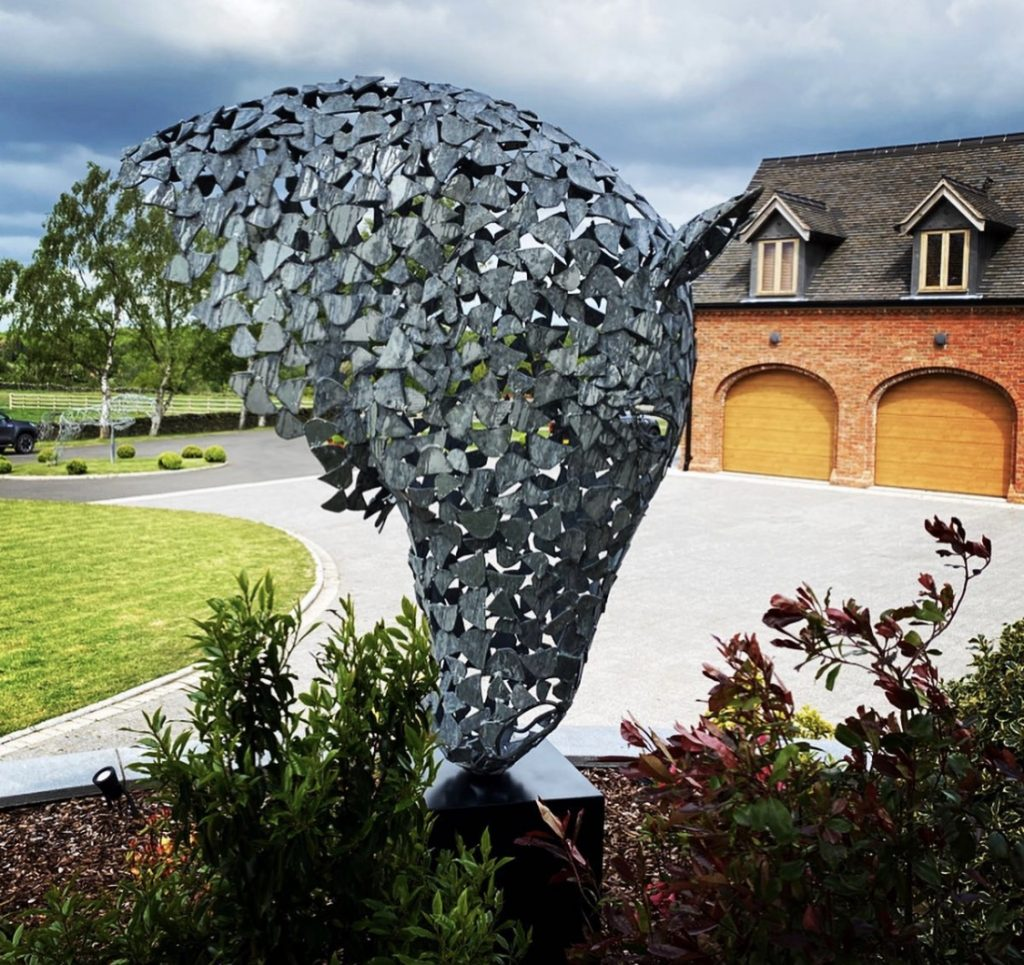 silver horse head sculpture mounted in front of a house