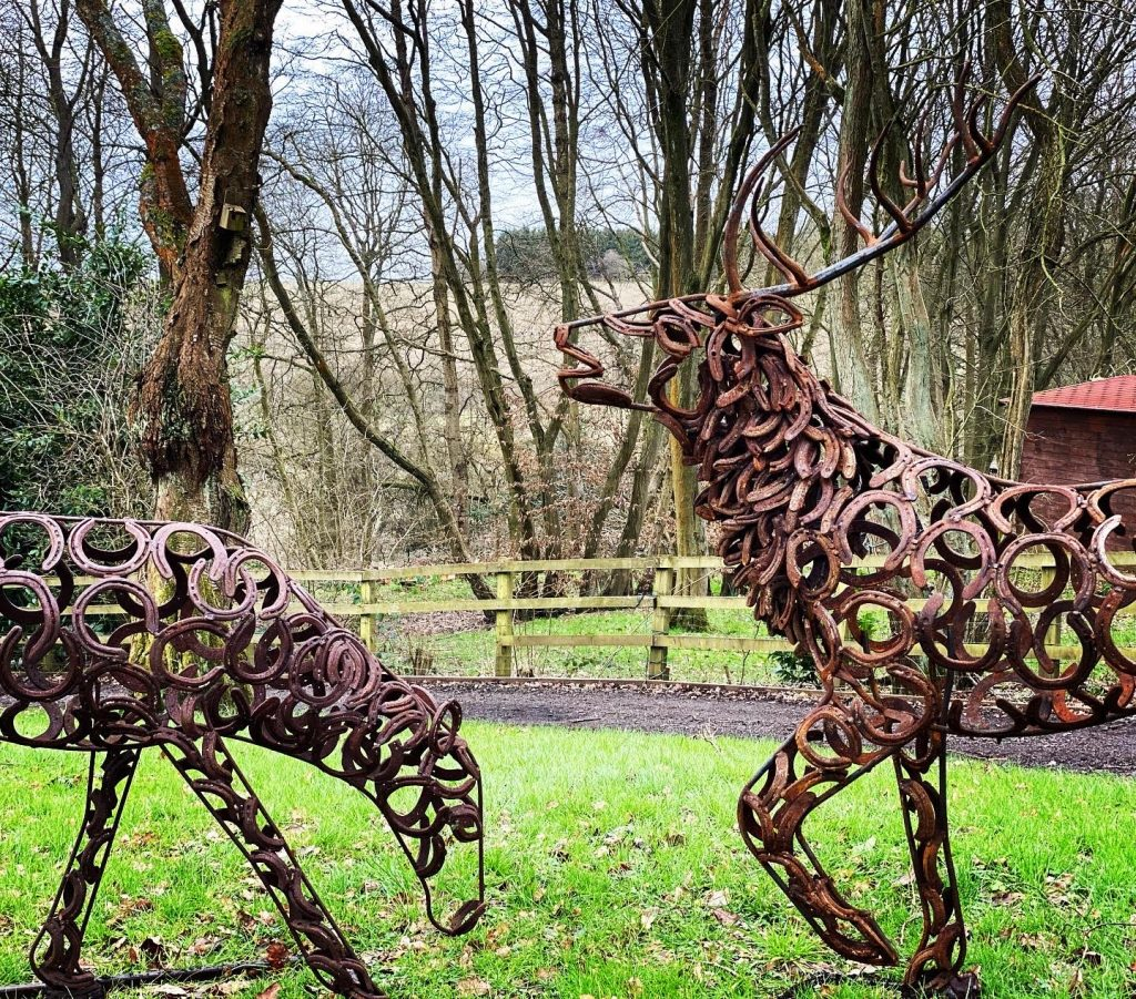 Two Stag Sculptures In A Field