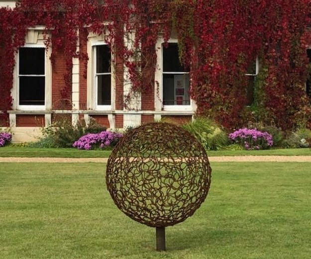 bronze horse shoe sphere sculpture in front of a house