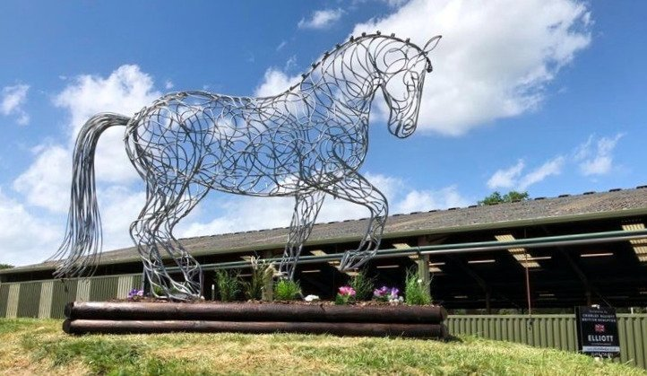 side view of a silver horse walking sculpture
