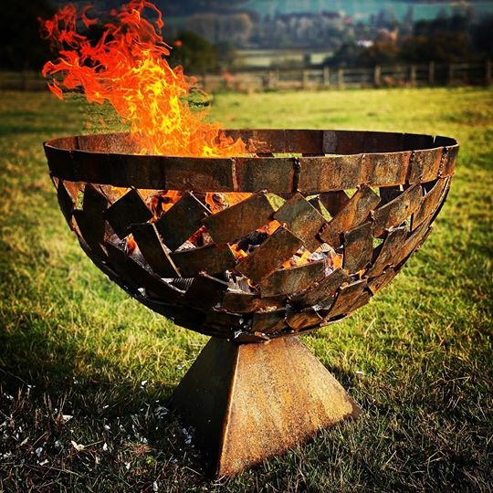 close up of medium sized fire pit in field
