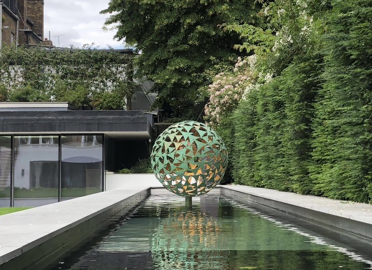large green sphere sculpture in water feature