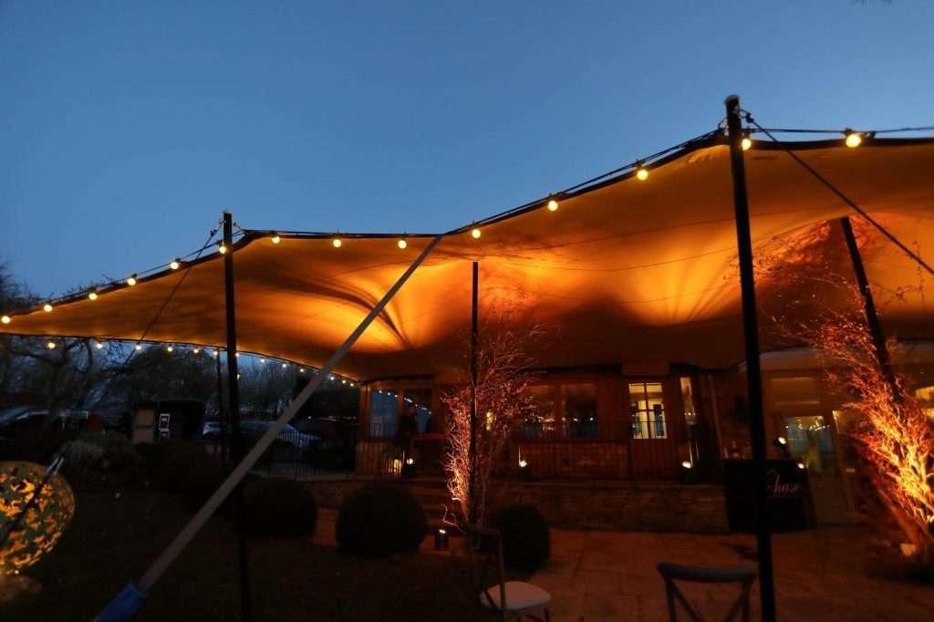 a lit up tent over a porch