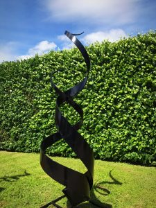 Black Spiral Abstract Sculpture In Front Of Hedge