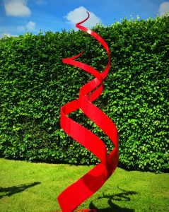 Red Spiral Abstract Sculpture In Front Of Hedge