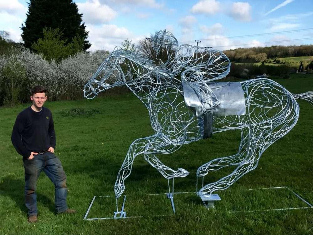 Man Standing Next To Horse and Jokey Sculpture